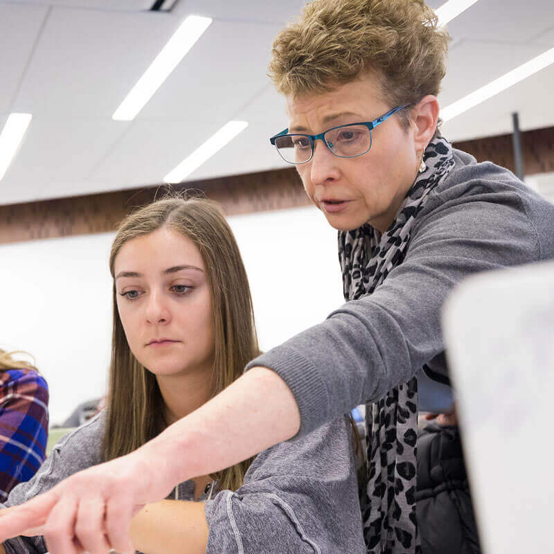 Mary Schramm, Associate Professor of Marketing, works with Sydney Kenyon during class in the Lender School of Business.