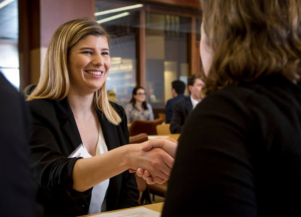 Student shakes hands with an alumni at a networking event