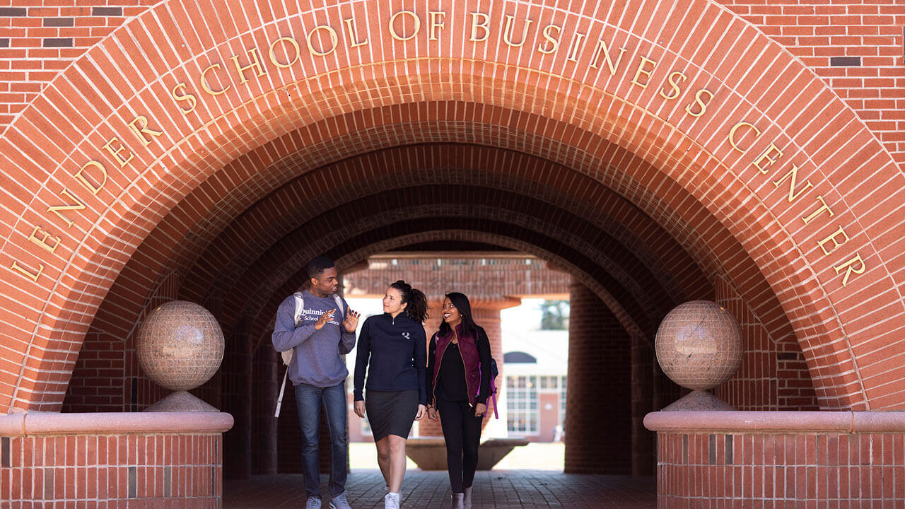 Students walk under the brick arch of the School of Business Center