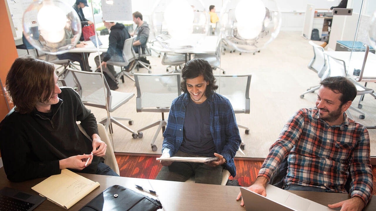 Three students sit at a table in the Center for Innovation and Entrepreneurship