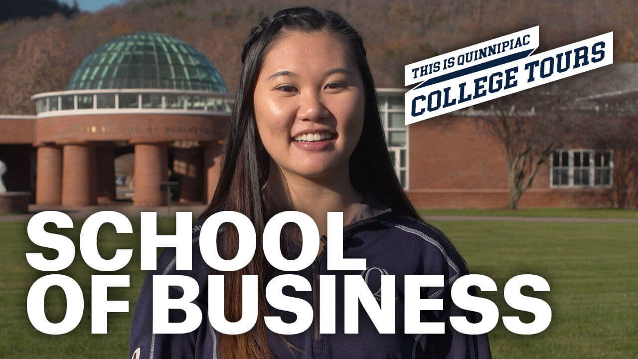 Student standing outside the School of Business, starts video tour