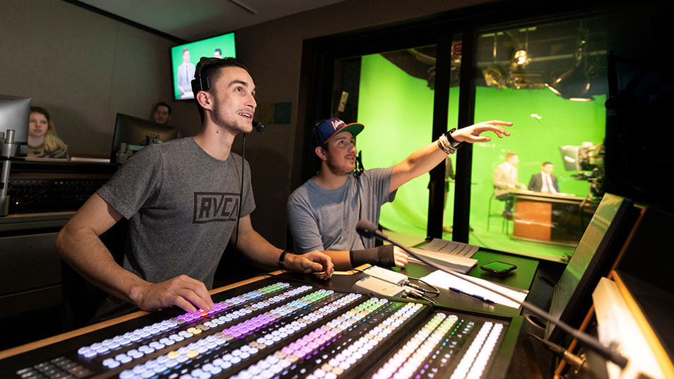 Two students wearing headsets sit behind a large control board in the McMahon Center communications room