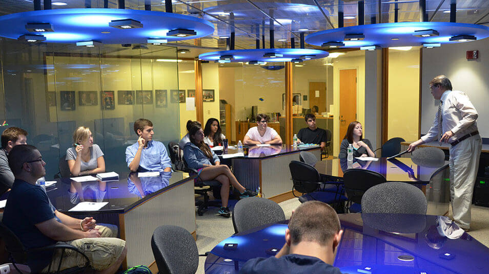 A full class in session in the Media Innovations Classroom with blue light fixtures