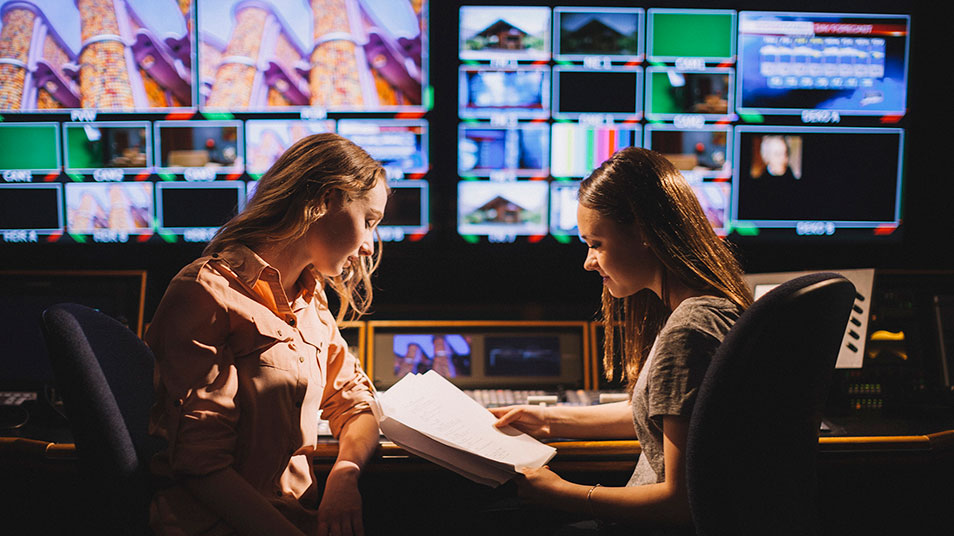 Two students go over notes together as they sit in the control room of QU's television studio