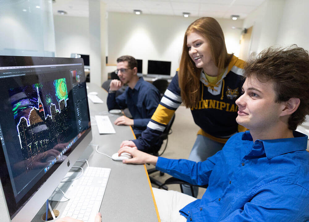 A communications student works on a graphic design on a computer monitor while a classmate smiles over his shoulder