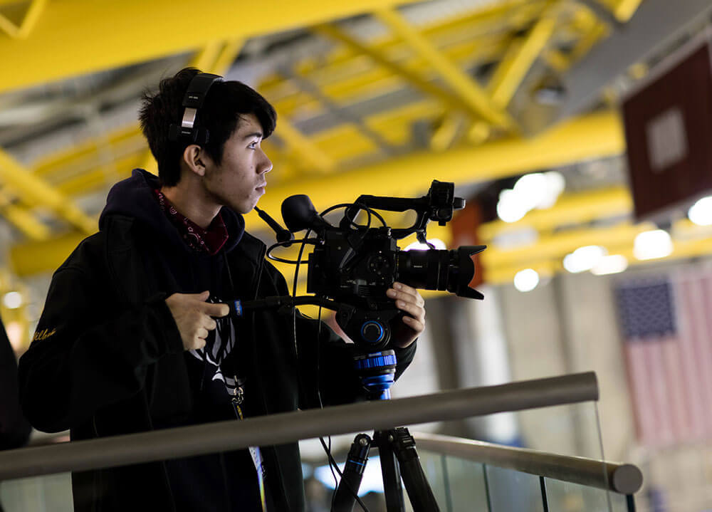 A student wearing headphones and operating a large camera on a tripod films a pregame show at the hockey arena