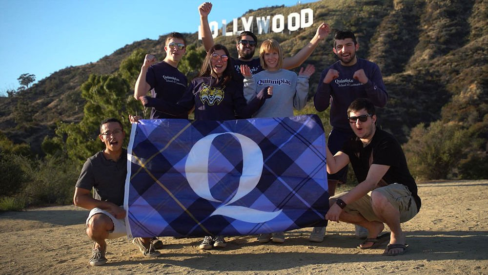Quinnipiac students pose in front of the Hollywood sign holding a large Q flag