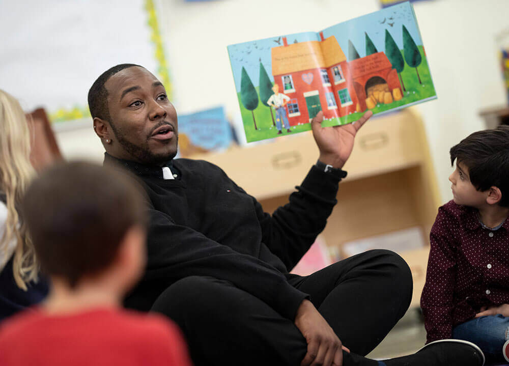 A School of Education graduate student reads a colorful picture book out loud to a group of elementary students