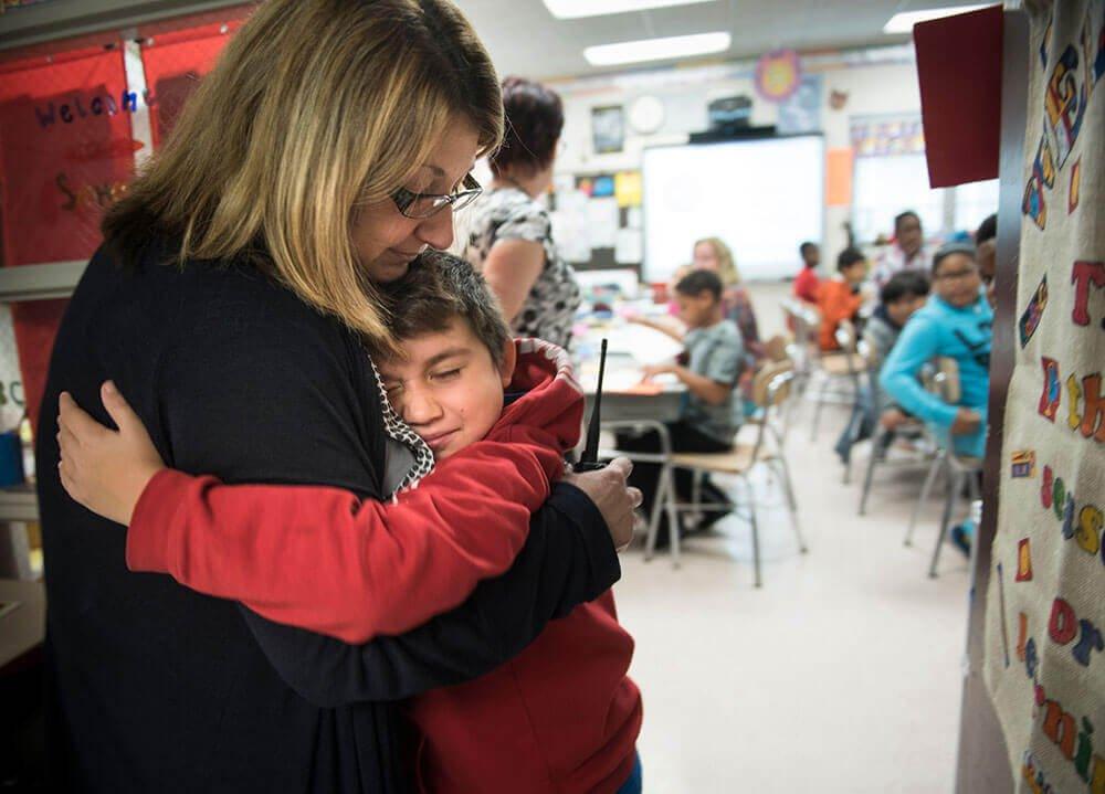 Principal Stacie D'Antonio hugs an elementary school student wearing a red hoodie