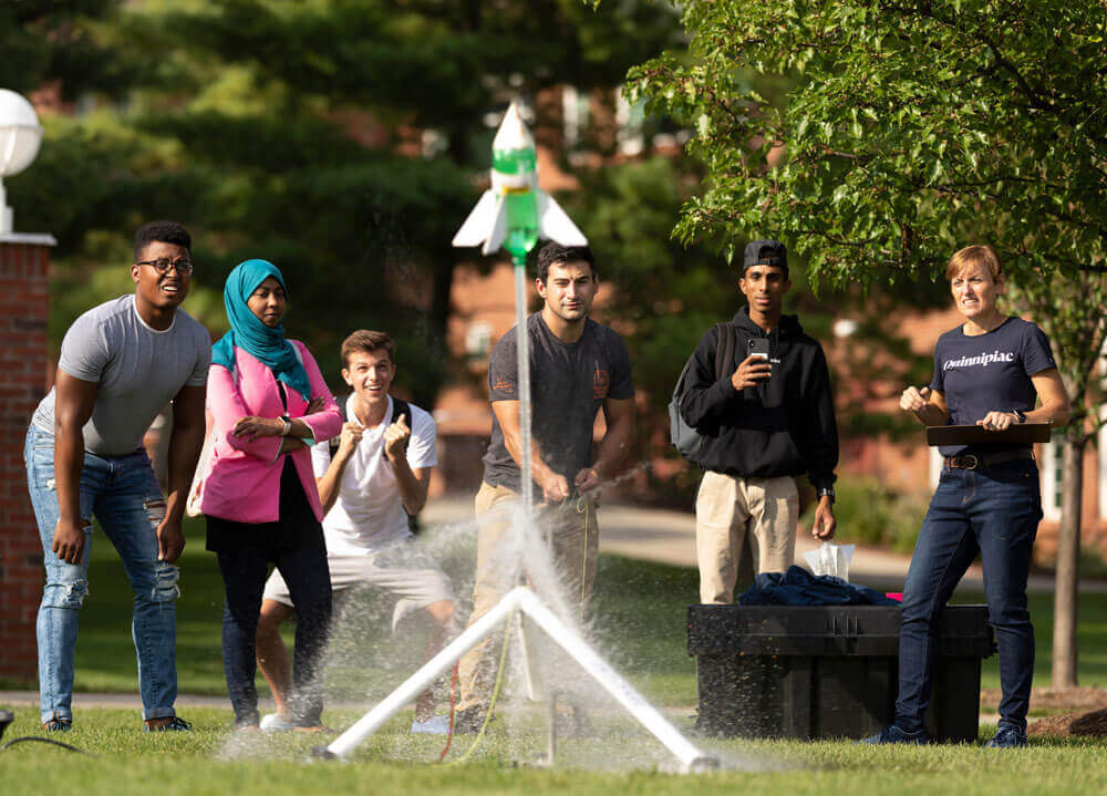 Students and a professor launch a bottle rocket they made into the air