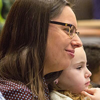 Sarah Obuchowski smiles and holds her daughter while attending a lecture