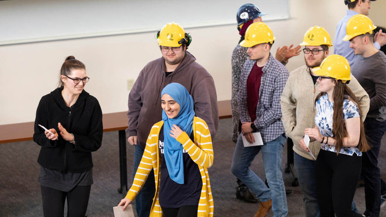 A group of students wearing Quinnipiac-branded hard hats