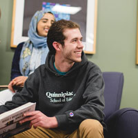Student Michael Thorpe holding a textbook and smiling