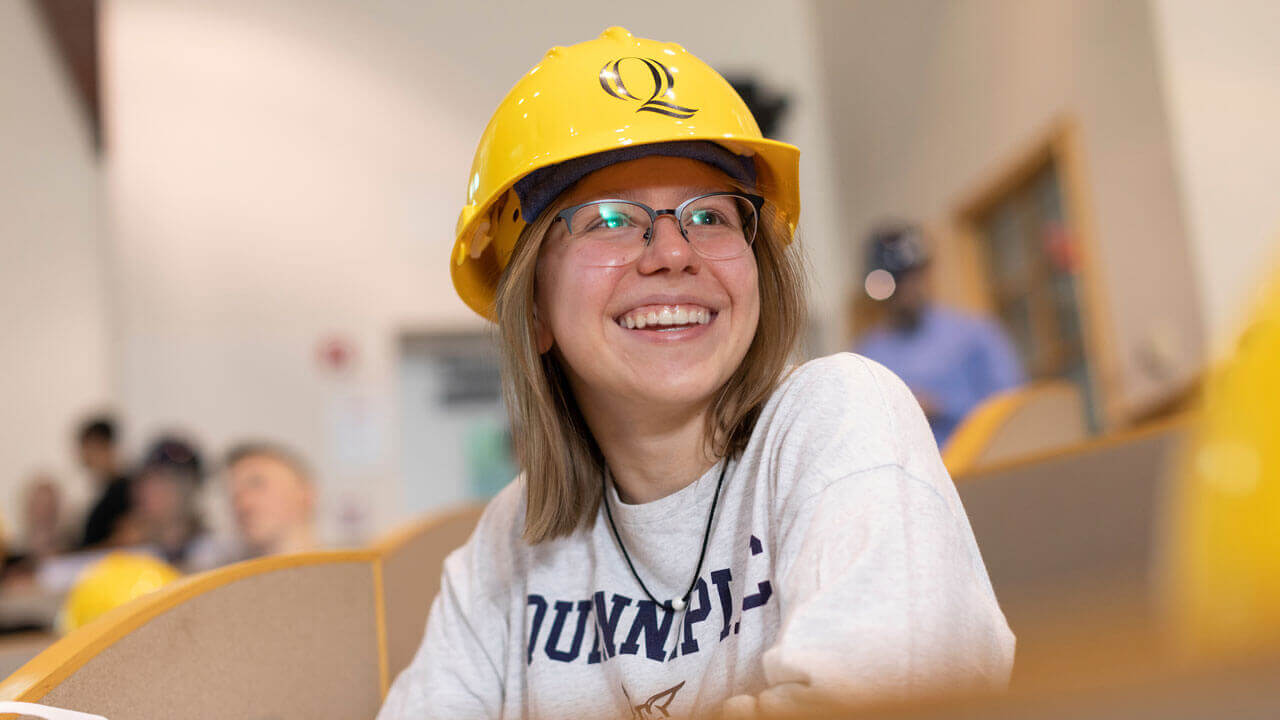 Student smiling while wearing Quinnipiac-branded hard hat