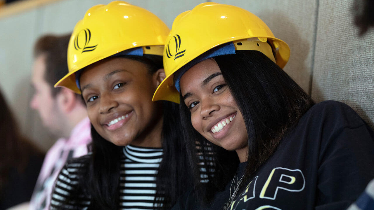 Two students smile while wearing Quinnipiac-branded hard hats