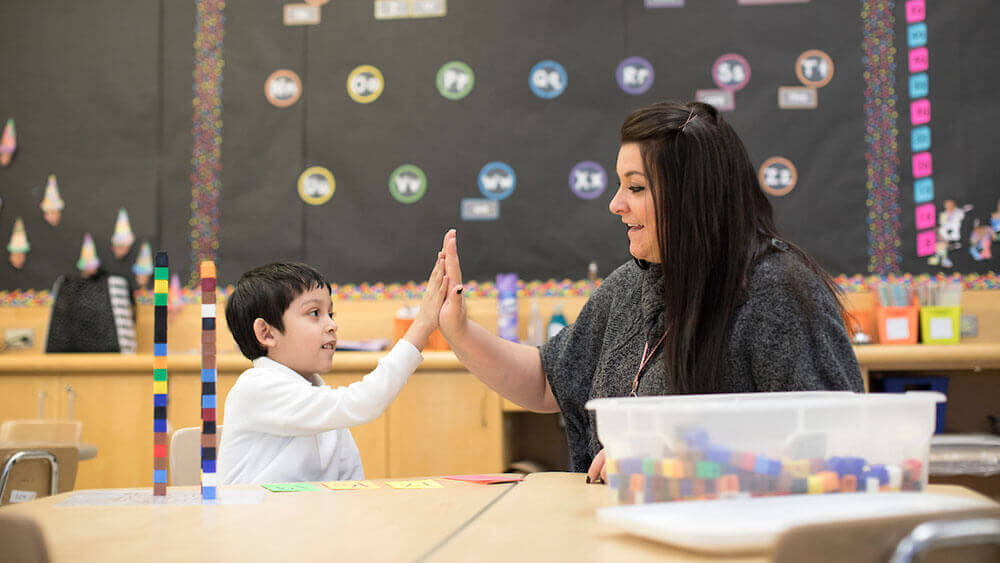 Education alumni Marisa Laudano hi-fives a kindergartner in a classroom