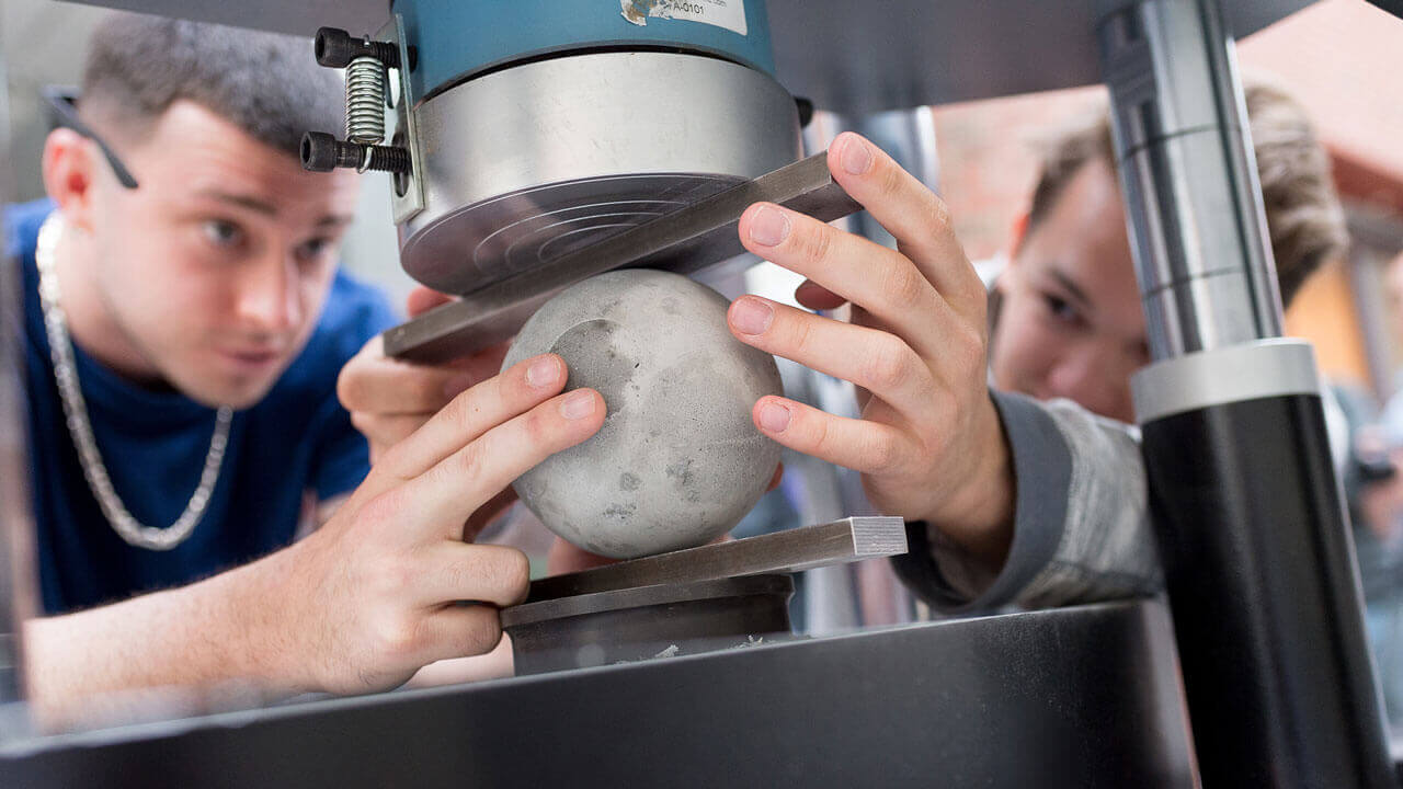 Students examine a bowling ball on a machine