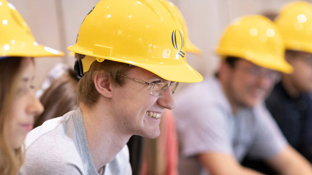 A student smiles during the hard hat ceremony