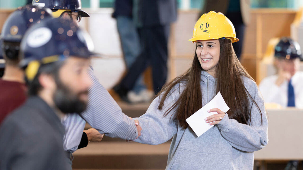 Student smiling while wearing a hard hat.