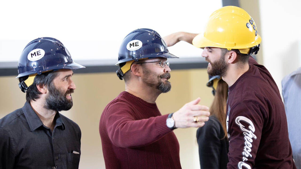 A student embraces a professor during the hard hat ceremony