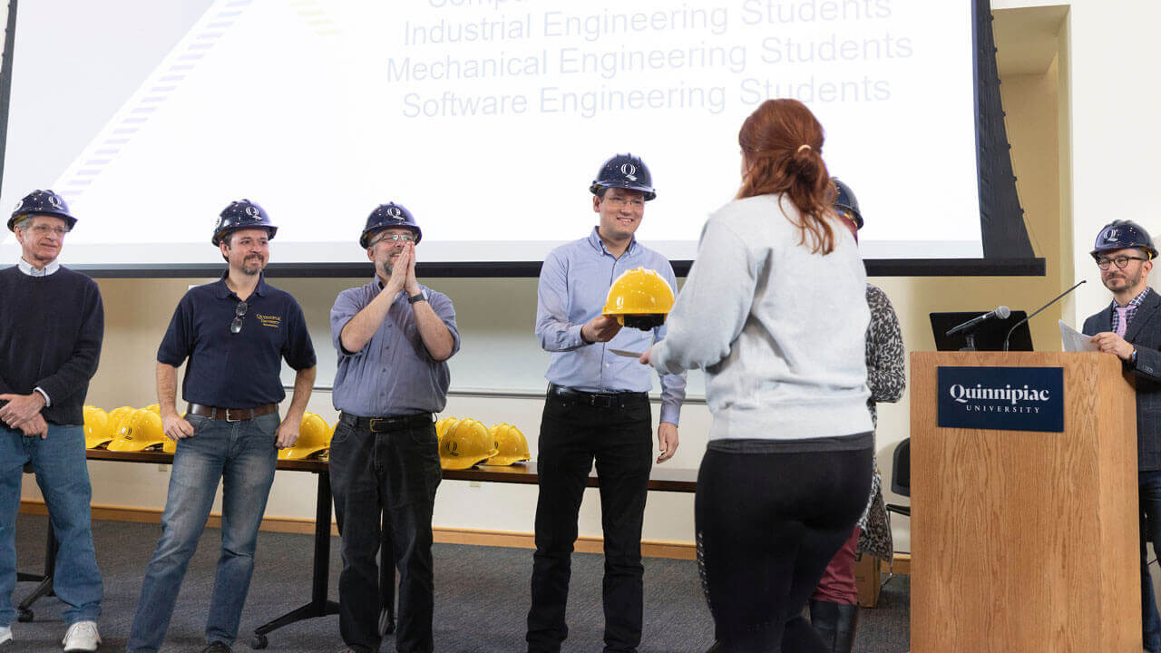 A faculty member passes a hard hat to a student