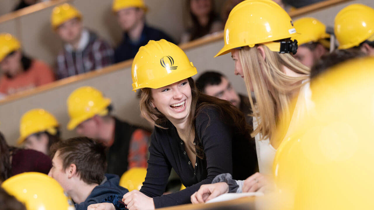 Two students smiling at each other while wearing Quinnipiac-branded hard hats
