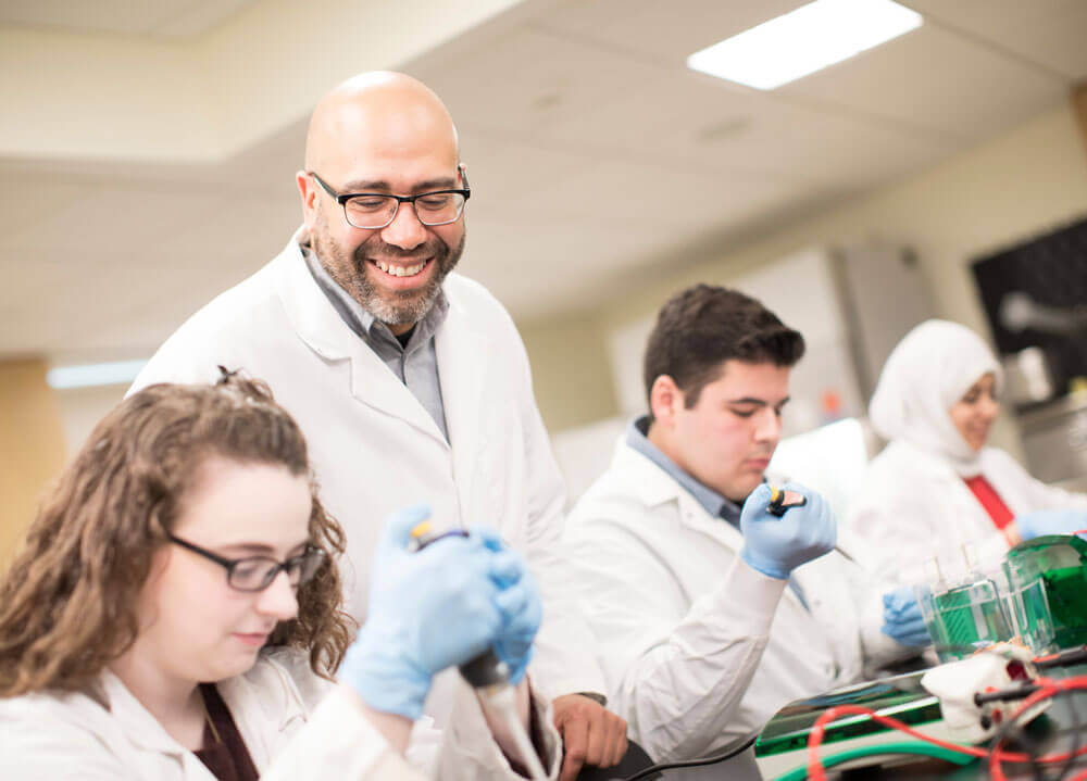 Professor smiles at students as they complete a lab