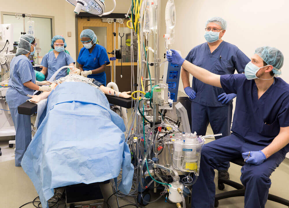A group of students and the professor work in an operating room