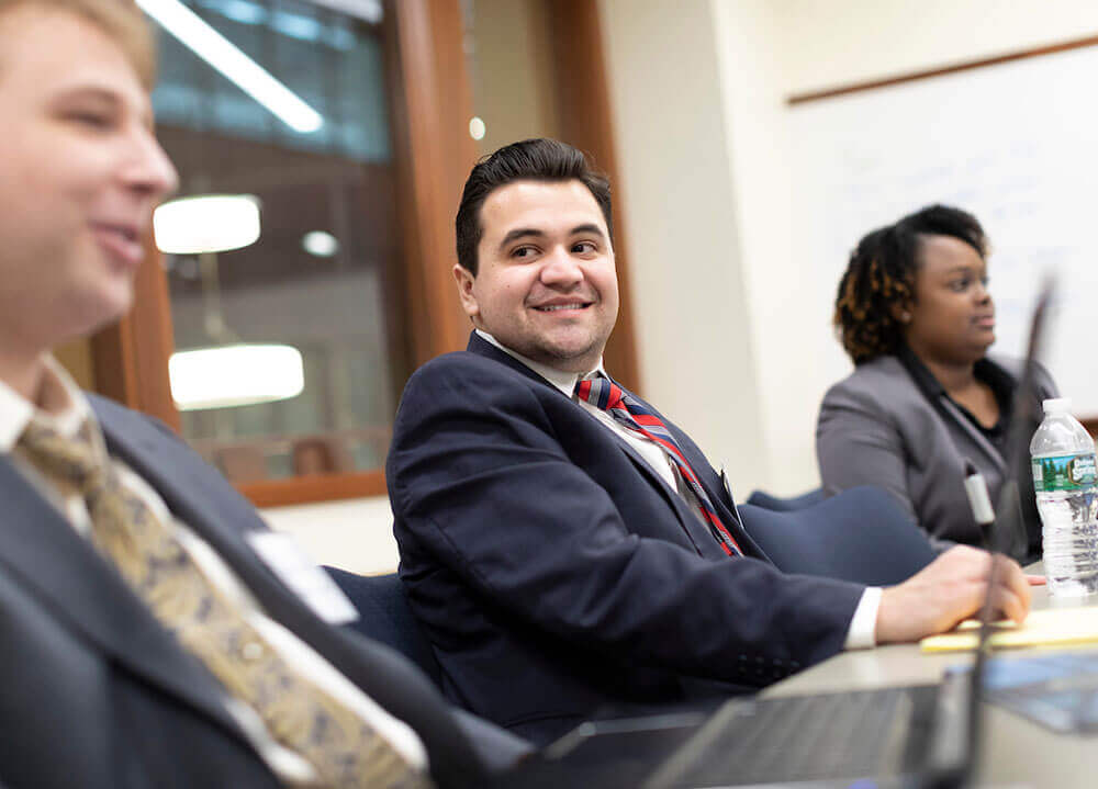 Three law students pictured sitting side-by-side and smiling during a class workshop