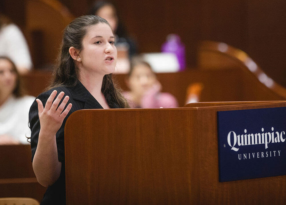 A law student pleads her case from behind a Quinnipiac University lectern in the ceremonial courtroom
