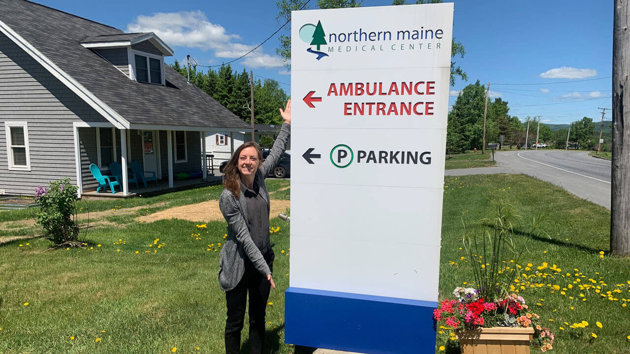A woman smiles and points to signage outside the Northern Maine Medical Center.