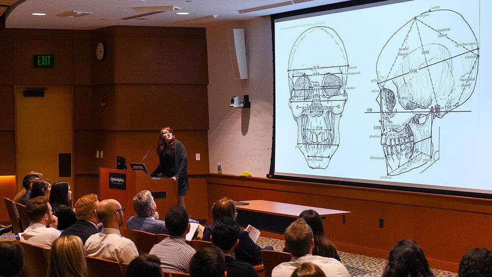 Medical student Katelyn Norman stands in front of a large display of a skull sketch as she presents her capstone findings