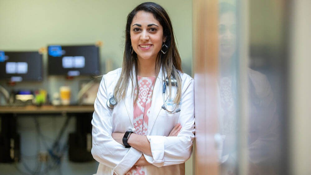 Med student Rana Alhaldi poses in the doorway of her office wearing her white coat and stethoscope
