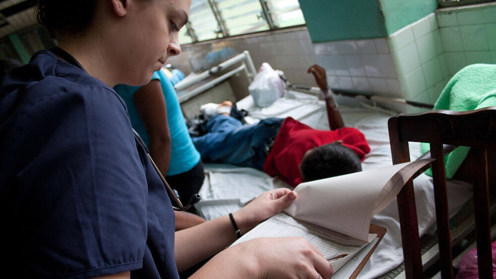 A nursing student checks on a local patient in a Nicaraguan hospital