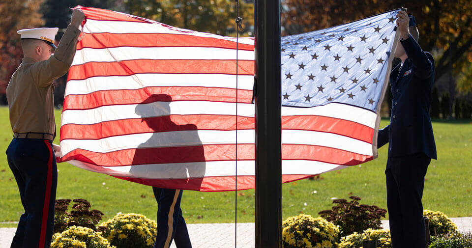 Three student veterans participate in a flag raising ceremony