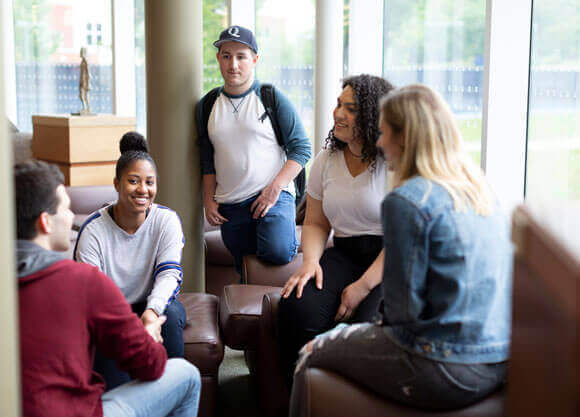 A group of undergraduate students talk together in the library