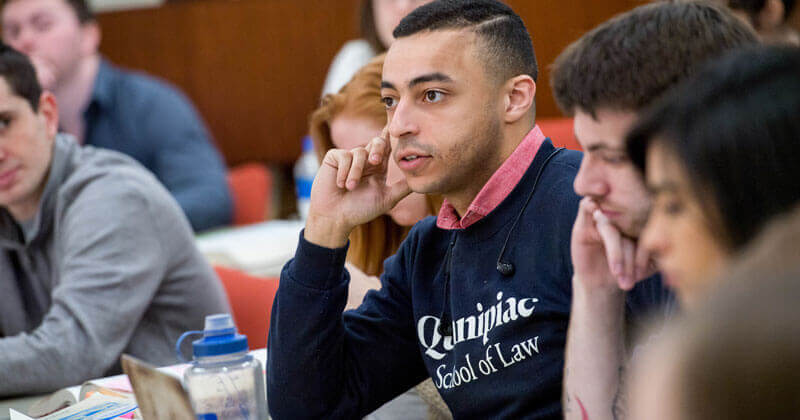 A law student wearing a Quinnipiac Law shirt sits among peers during class