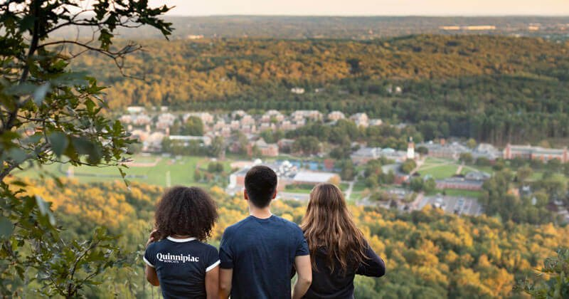 Three students look out on the Mount Carmel Campus from the Sleeping Giant peak