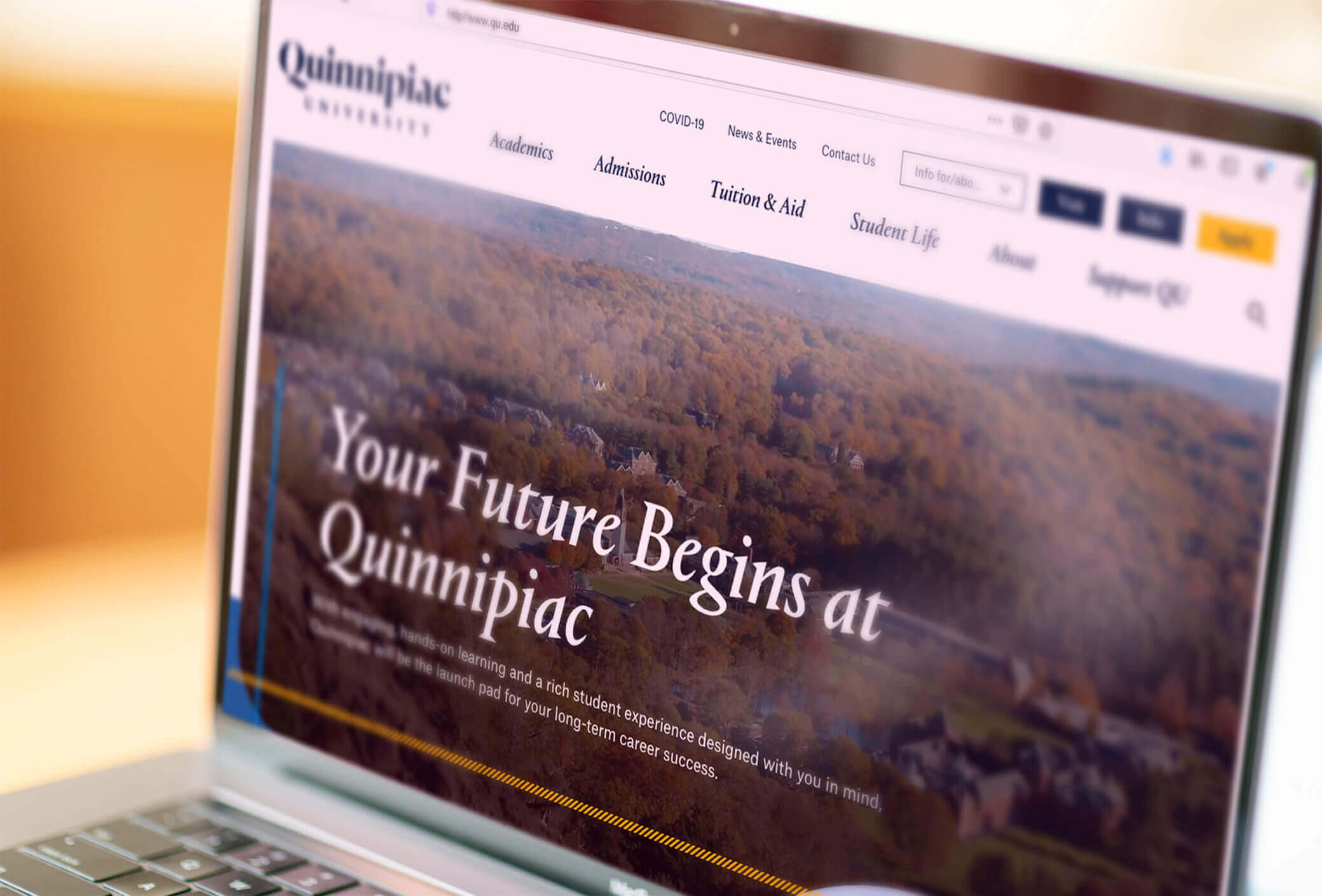 Laptop screen showing the landing page of Quinnipiac's website..