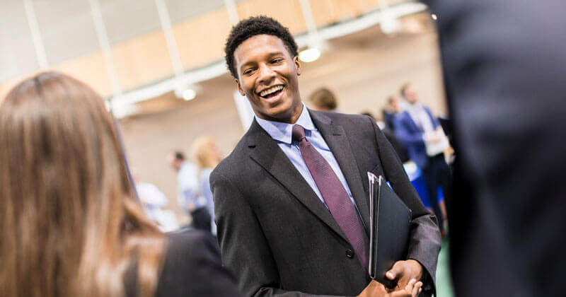 A student wearing a suit smiles as he talks to someone during a career fair