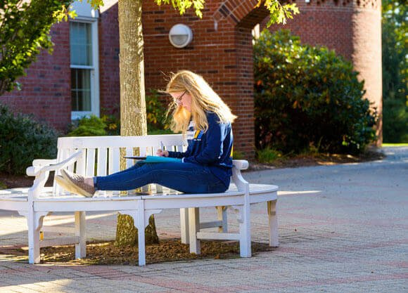 A student studies outside Echlin Center where undergraduate admissions is housed
