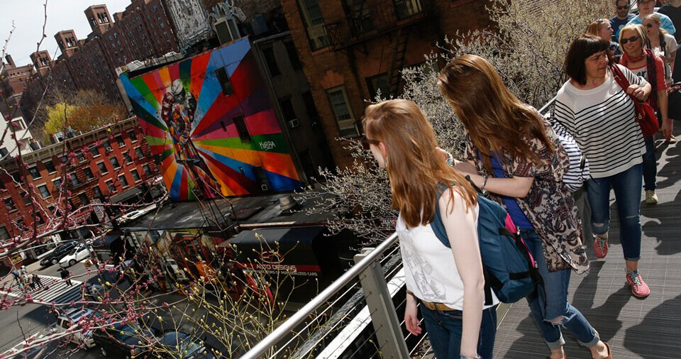 Several students on the New York high line look at a colorful mural in the distance