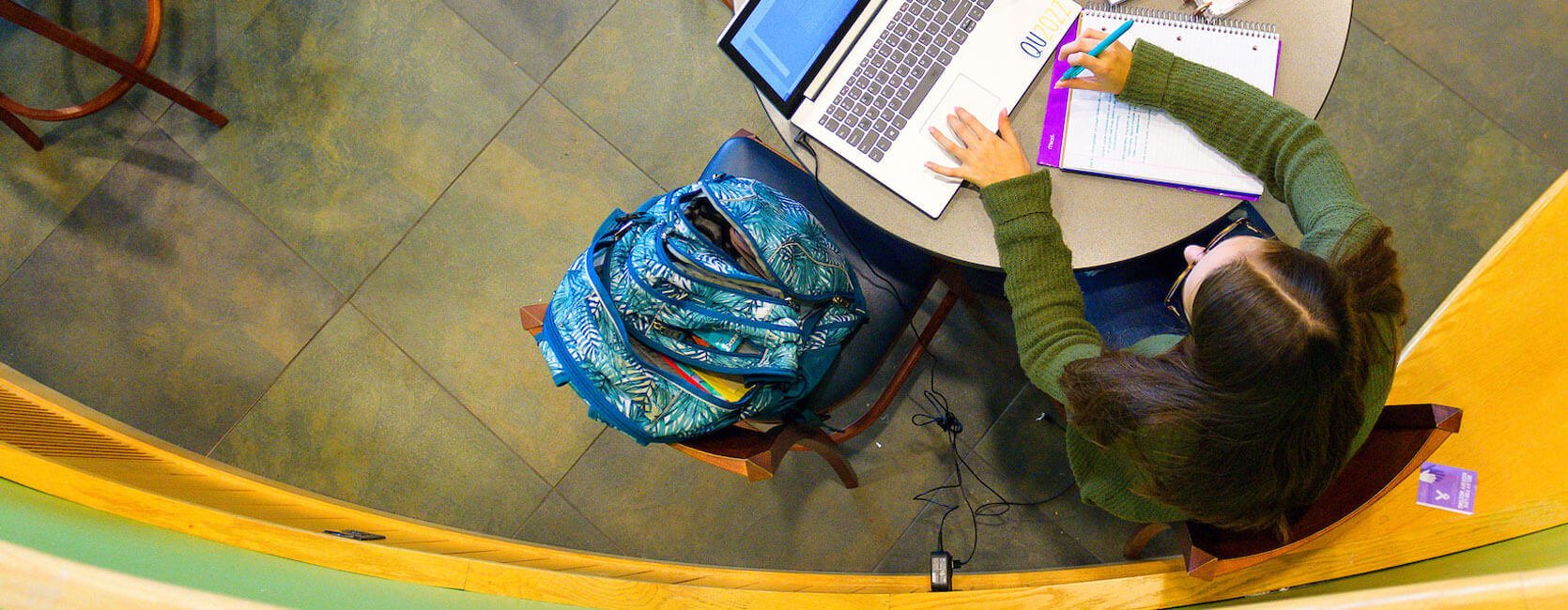 A student works at her laptop in the student center piazza