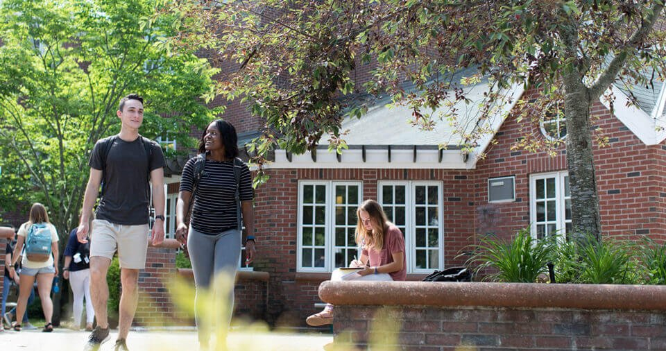 Two students talk as they walk by residence halls