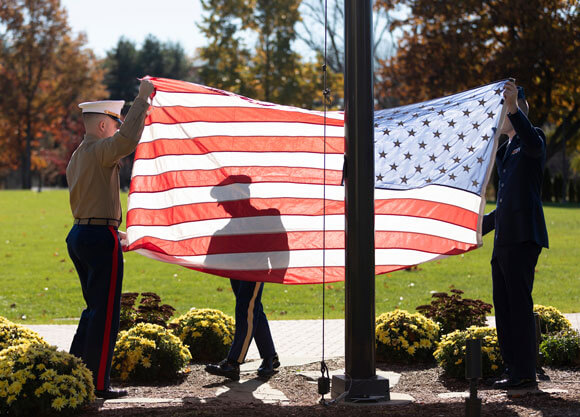 Three student veterans raise an American flag during a ceremony