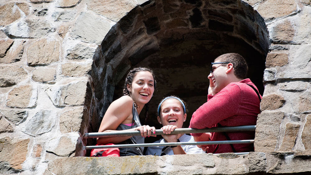 Quinnipiac medical students Marisa Goshorn and Kat Chinnici and Cheshire transitional student Brent Bouteiller look out from the castle at Sleeping Giant State Park on Thursday, June 2, 2016 as part of an interprofessional service learning course. The popular Sleeping Giant Tower Trail offers a 3-mile out and back path that offers scenic views of the Mount Carmel Campus.