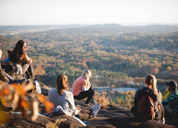 A group of students sit on the top of Sleeping Giant during a Reflective Hike to Yoga session.