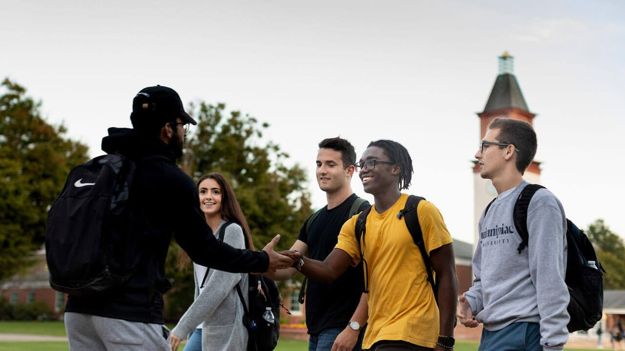 A group pf students greet each other on campus