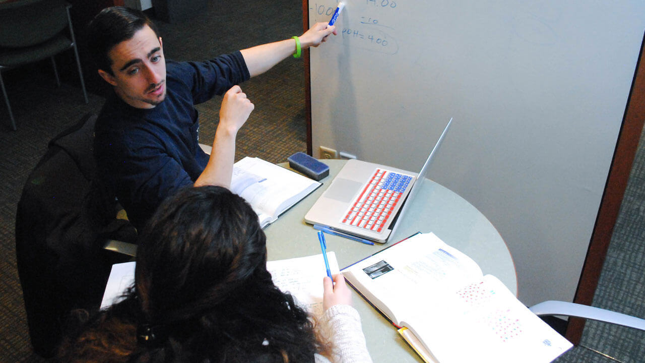 A student and tutor sit at a table with books while looking at a whiteboard.