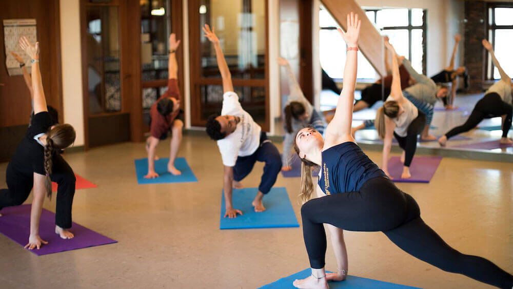 Instructor Lily Shemo leading a yoga fitness class in the studio space in the Rocky Top Student Center on the York Hill Campus